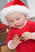 Baby in Father Christmas hat, messy with chocolate