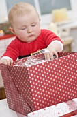 Baby reaching into opened Christmas parcel