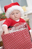 Baby in Father Christmas hat reaching into opened parcel