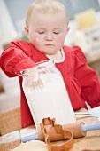 Toddler reaching into jar of flour