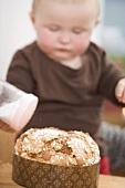 Toddler sprinkling sugar on almond cake