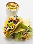 Tacos filled with beans & sweetcorn, vegetable dip in small bowl