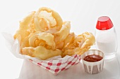 Deep-fried onion rings in cardboard container, ketchup, salt