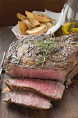 Sirloin steak, partly sliced, potato wedges in background