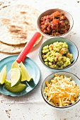 Tortillas, guacamole, salsa, grated cheese and lime wedges