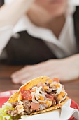 Mince taco, woman in background