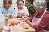 Grandmother telling grandchildren how to shape vanilla crescents