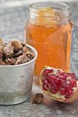 Roasted almonds, wedge of pomegranate and jar of honey