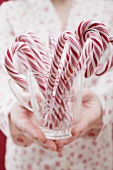 Woman holding glass of candy canes