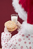 Woman in Father Christmas hat holding cookies & glass of milk