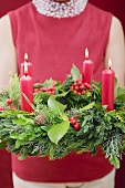 Woman holding Advent wreath with four burning candles