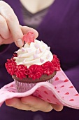 Woman holding Valentine's Day cupcake on paper napkin