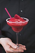 Mann hält ein Glas Strawberry Daiquiri