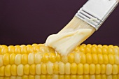 Brushing corn on the cob with butter