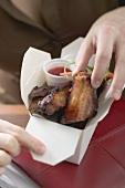 Frau nimmt glasierte Schweinerippchen aus Take-Out-Behälter
