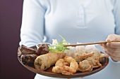 Woman holding Asian appetiser platter and chopsticks