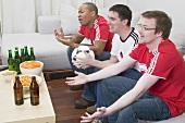 Drei Fussballfans mit Knabberzeug und Bier beim Fernsehen