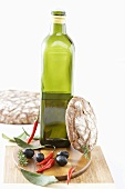 Bottle of olive oil, olives, chillies and rustic bread