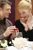 Mann schenkt Frau Brilliantring beim romantischen Essen