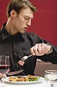 Impatient man eating steak in a restaurant