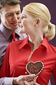 Man giving woman chocolate heart with the words Be Mine