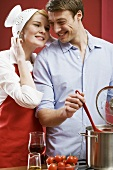 Couple cooking pasta with tomatoes