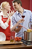Couple cooking spaghetti & tomatoes, woman holding glass of wine