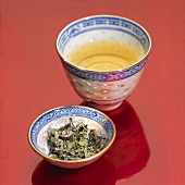 Green tea in bowl and tea leaves in small dish
