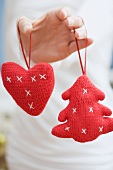 Hand holding two knitted Christmas tree ornaments