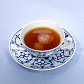 Tea with sugar crystals in cup and saucer
