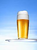 Glas helles Bier auf Tablett