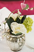 Posy of flowers with pink heart in silver vase on laid table