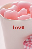 Pink heart-shaped sweets in beaker for Valentine's Day