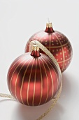 Two red Christmas baubles with gold stripes and spots