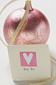 Pink Christmas bauble with gold ribbon and card