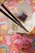 Reis, Sojasauce und Essstäbchen im Take-Out-Behälter