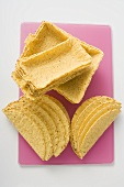 Assorted taco shells on pink chopping board