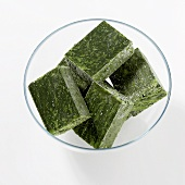 Cubes of frozen spinach in a glass bowl