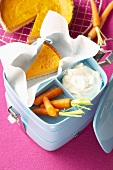 Carrot pie, cream and fresh carrots in lunch box