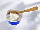 Ricotta in plastic tub with wooden spoon