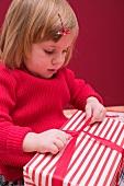 Small girl undoing ribbon on Christmas parcel