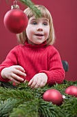 Small girl decorating Christmas tree with red baubles