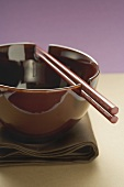 Lacquer bowl with chopsticks on brown cloth (Asia)