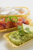 Guacamole, tomato salsa and sour cream in taco shells