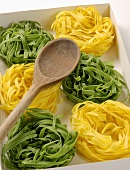 Green & yellow ribbon pasta nests with wooden spoon in box