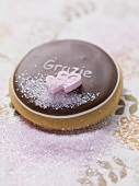 Biscuit with chocolate icing, sugar hearts & the word Grazie