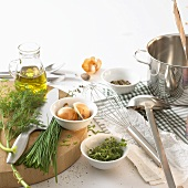 Still life with herbs, onions, oil and kitchen utensils