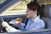 Young woman eating croissant while driving