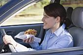Junge Frau isst Croissant beim Autofahren