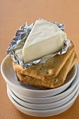 Processed cheese in foil on crackers in stacked dishes
